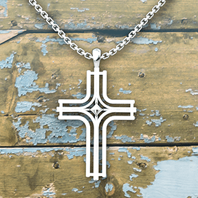 Radiant Cross Sterling Silver Necklace on an 18 inch chain with an old wood background