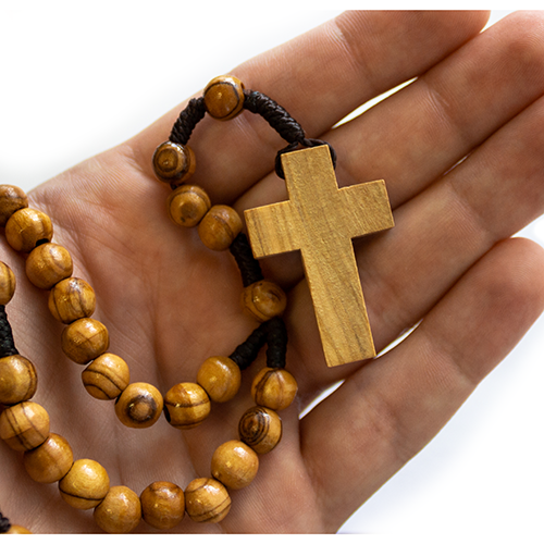 olive wood rosary shown inside a palm