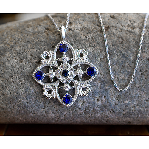 "Antique Blue Sapphire September Birthstone Sterling Silver Cross Pendant - With 18"" Sterling Silver Chain on a rock"