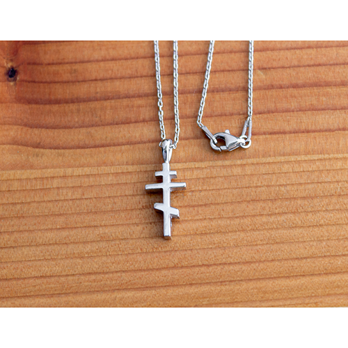 Saint Andrew Cross Sterling Silver Pendant and 18 Inch Chain on a wooden table
