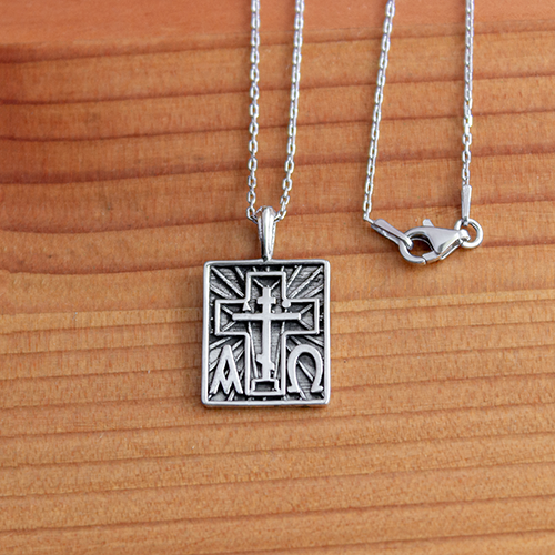 Alpha Omega & St Andrew Cross Sterling Silver Pendant - 18 Inch Chain on a wooden table
