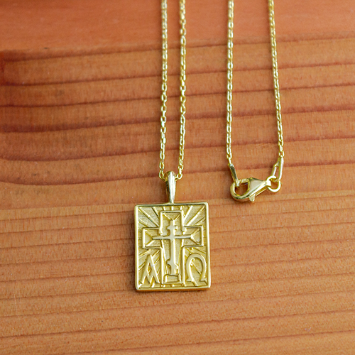 Alpha Omega & St Andrew Cross Gold-Plated Sterling Silver Pendant - 18 Inch Chain on a wooden table