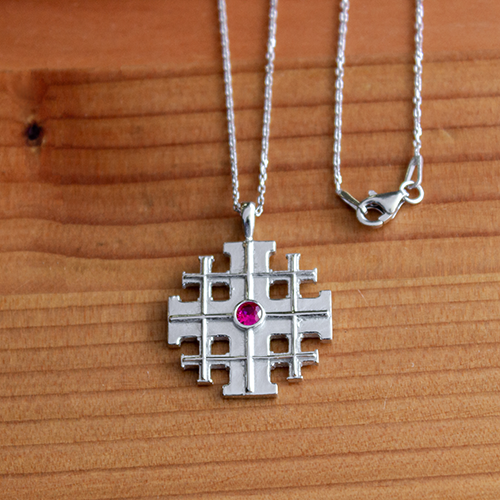 Jerusalem Cross with CZ Ruby, Sterling Silver Pendant - 18 Inch Chain on a wooden table
