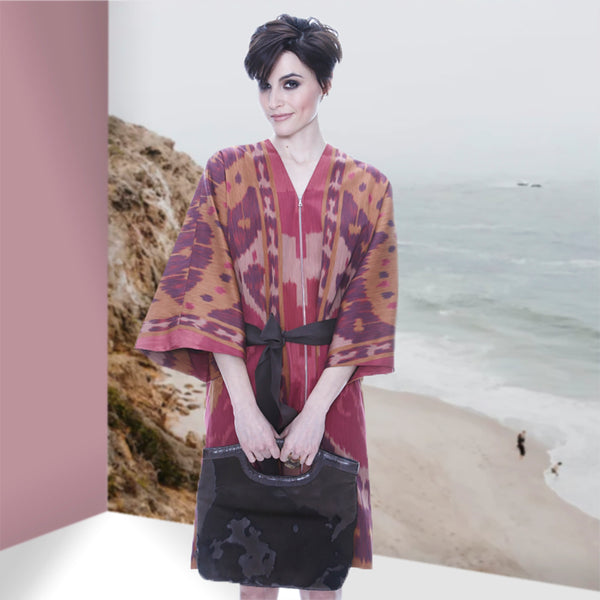Model in a red kimono, holding brown fold-over clutch - Darby Scott