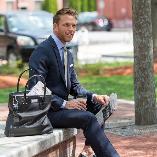 Man seated on an outdoor stone bench with a Darby Scott Essex tote bag