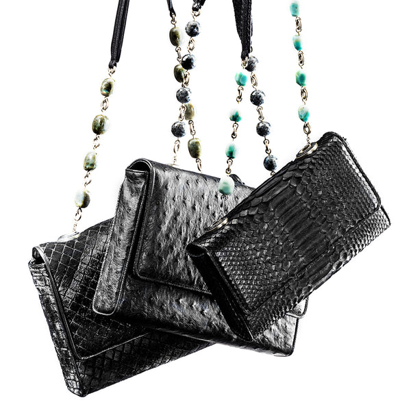 picture of 3 Darby Scott Black Chain and Jewel handbags hanging freely. One is embossed hair-calf one is ostrich and one is python