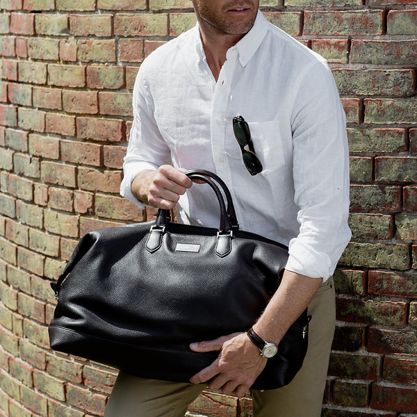 Man holding a black leather Aspen Duffle Bag - Darby Scott