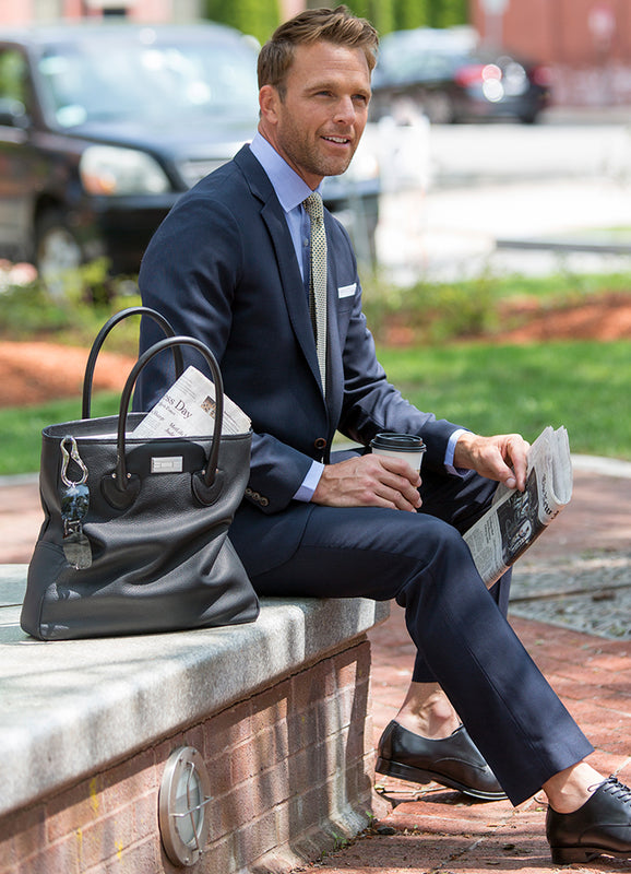 Model sitting outside. A Darby Scott Essex Leather Tote is beside him