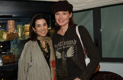 Designer Darby Scott and Geena Davis in front of case line of Darby Scott clutches and evening bags