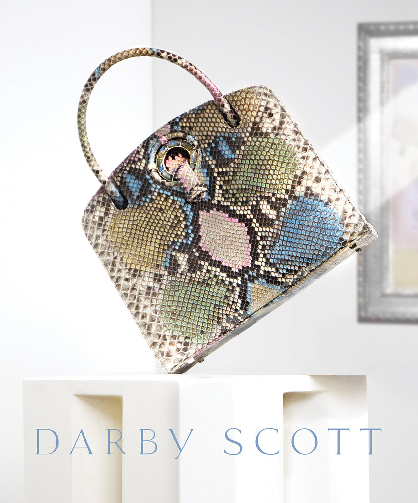 Pastel colored python Annette top handle bag on an ivory pedestal and Darby Scott Logo