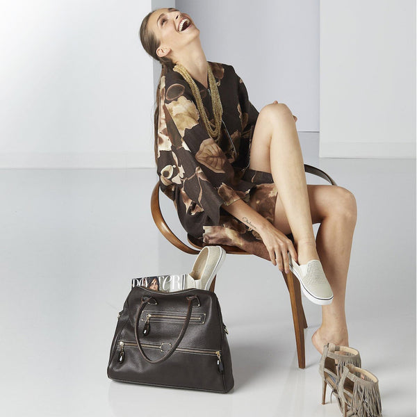 Model wearing Darby Scott Kimono and citrine necklace with leather Boston tote sitting next to them.