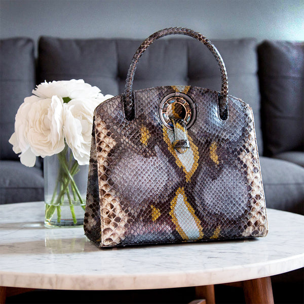 Darby Scott's Annette Top Handle Tote with Grommet Closure in Denim Blue Python on table with flowers