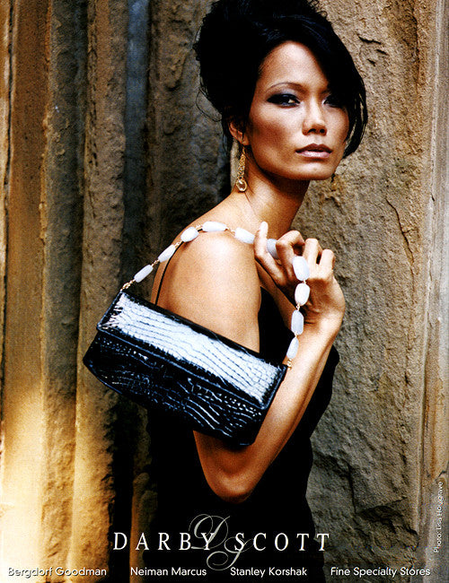 image of model in Darby Scott Gown holding a black alligator bag with semi-precious stone handle-from the Darby Scott chain and jewel collection