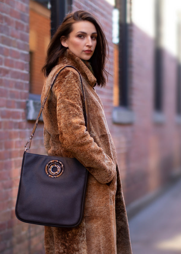 Woman outside in fur coat with chocolate leather Cloe Cross Body Tote over shoulder - Darby Scott