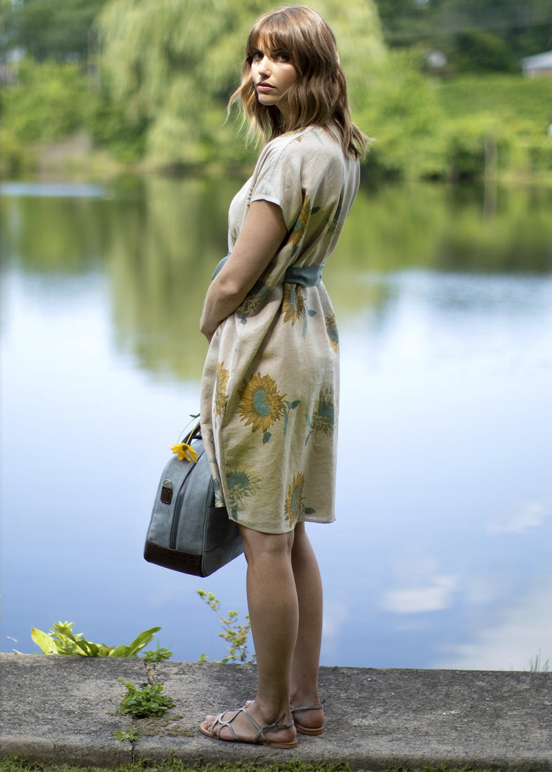 Darby Scott Model wearing sunflower Dress carrying a Newport travel bag