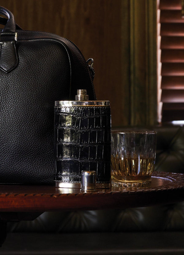 Black crocodile covered hip flask on table next to a glass - Darby Scott--alternate