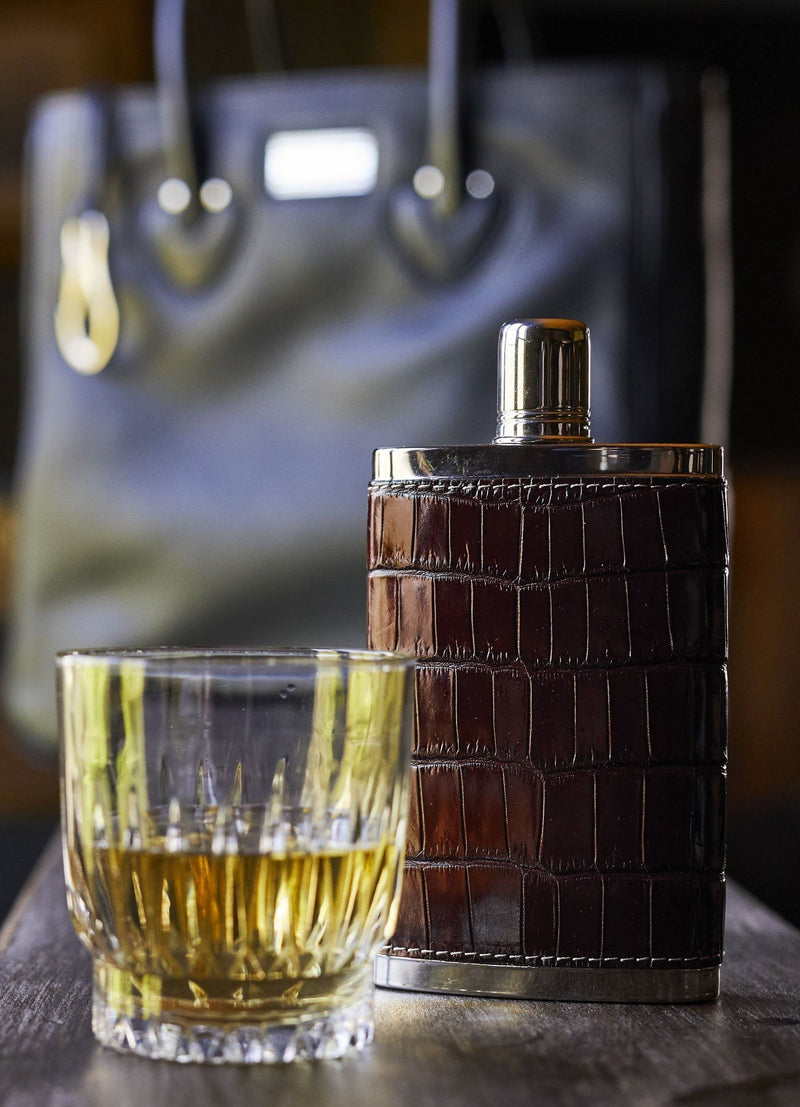 Brown Croc covered hip flask next to a glass - Darby Scott