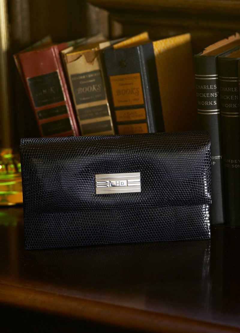 Navy Lizard Mini Monogram Clutch on shelf in front of books- Darby Scott