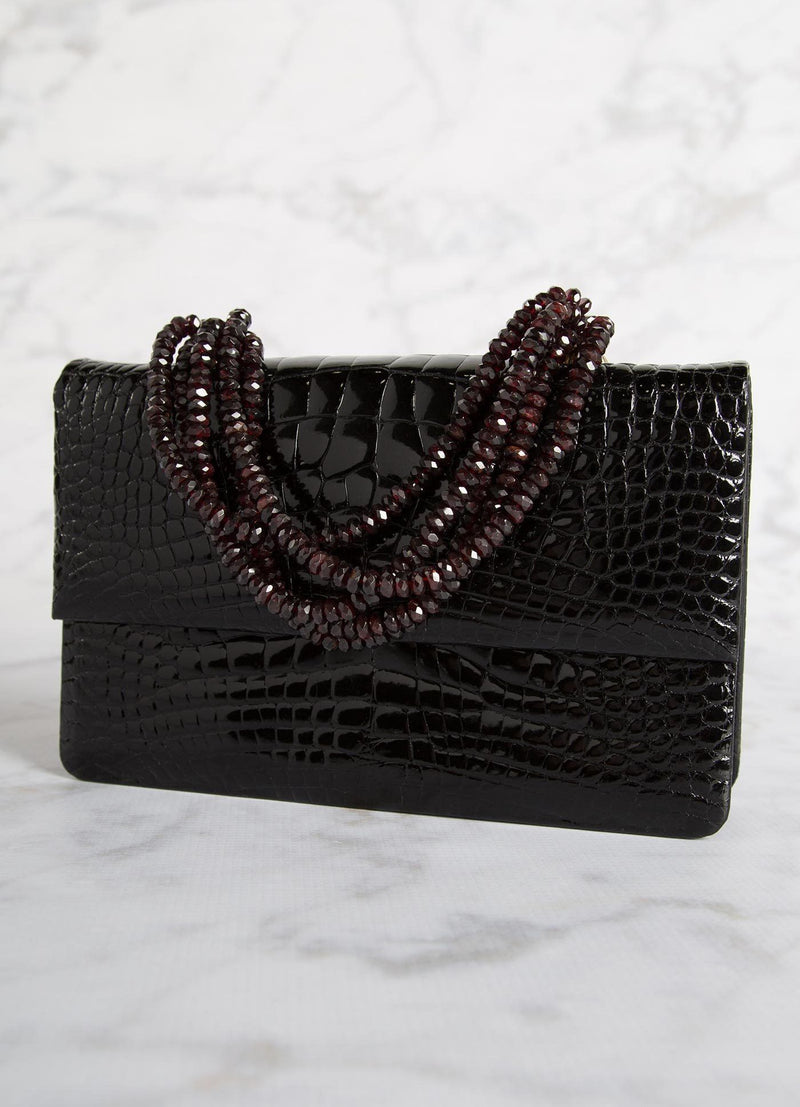 Angled view of Black Crocodile and Garnet Necklace Handbag - Darby Scott