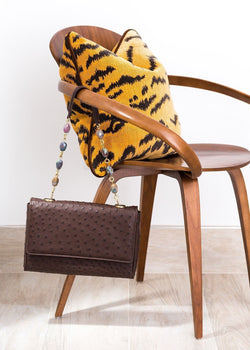 Brown ostrich chain & jewel shoulder bag hanging off a mid-century modern chair - Darby Scott
