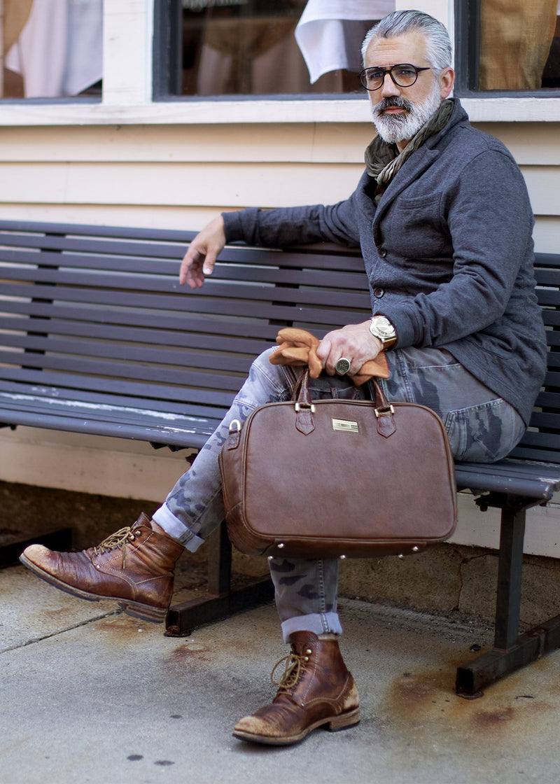 Man on bench with Brown Leather Newport Carry-on bag - Darby Scott