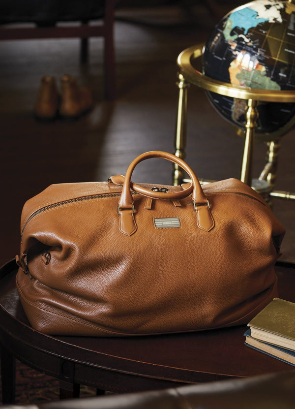 Leather Aspen Travel Bag in front of a globe in an office setting - Darby Scott--alternate