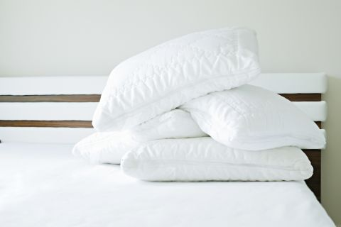 four new pillows stacked on the corner of a bed