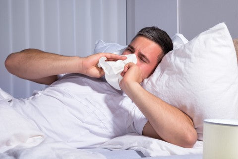 man suffering from allergies while in bed