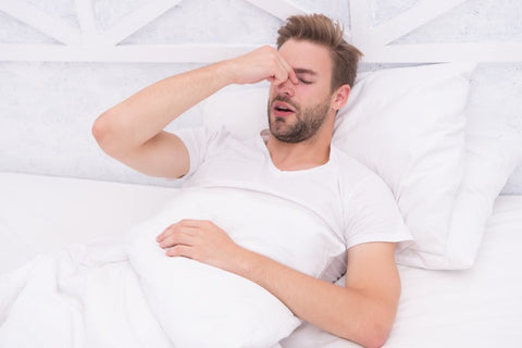 Young man lying on a bed suffering from the negative effects of using the wrong pillow