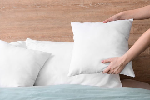 Woman fluffing pillows and placing them on her bed