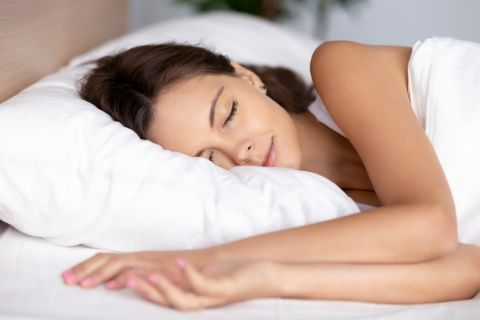 woman sleeping comfortably on her bed while using a new pillow