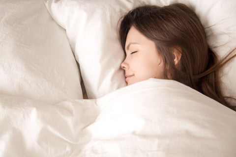 Young woman comfortably lying under blanket while using the right pillow