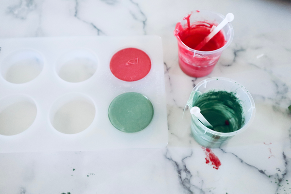 red and green soap that has been poured into a silicone soap mold