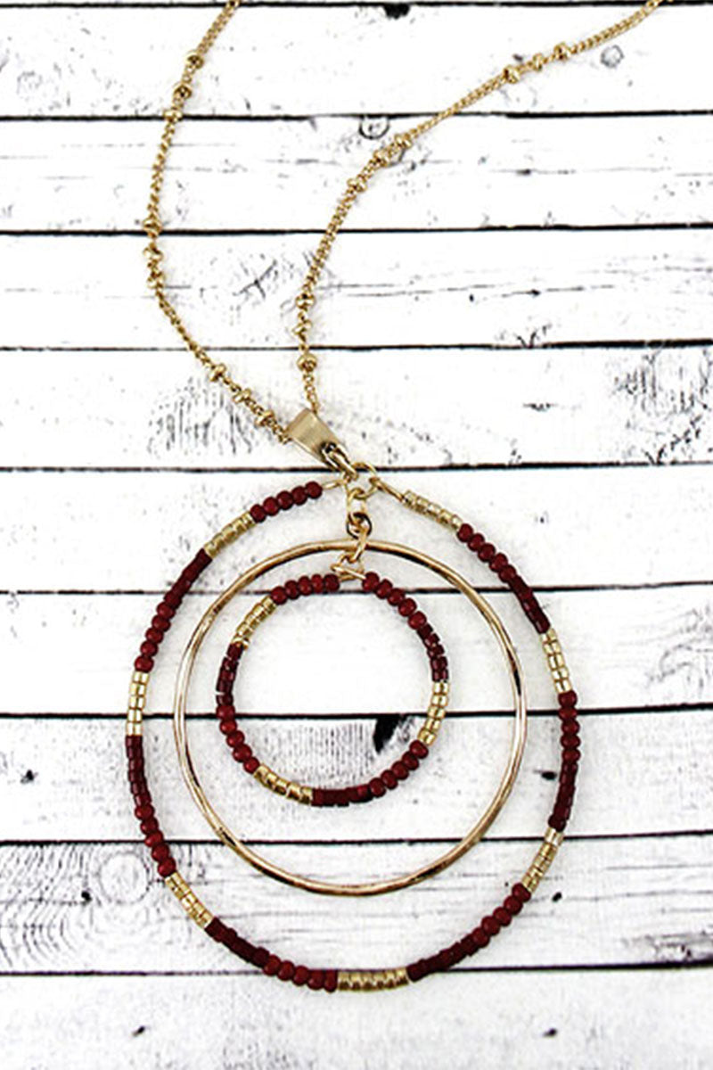 Crave Goldtone and Burgundy Seed Bead Orbital Circle Necklace
