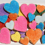 Heart shaped sugar cookies with rainbow colored sprinkles.