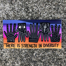 "Load image into Gallery viewer, A sticker which says ""there is strength in diversity"" with a multicolor background and several hands"