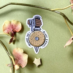 "a sticker with a hand holding a knife which goes through a bagel. Text says ""beware the blade and bagel"""