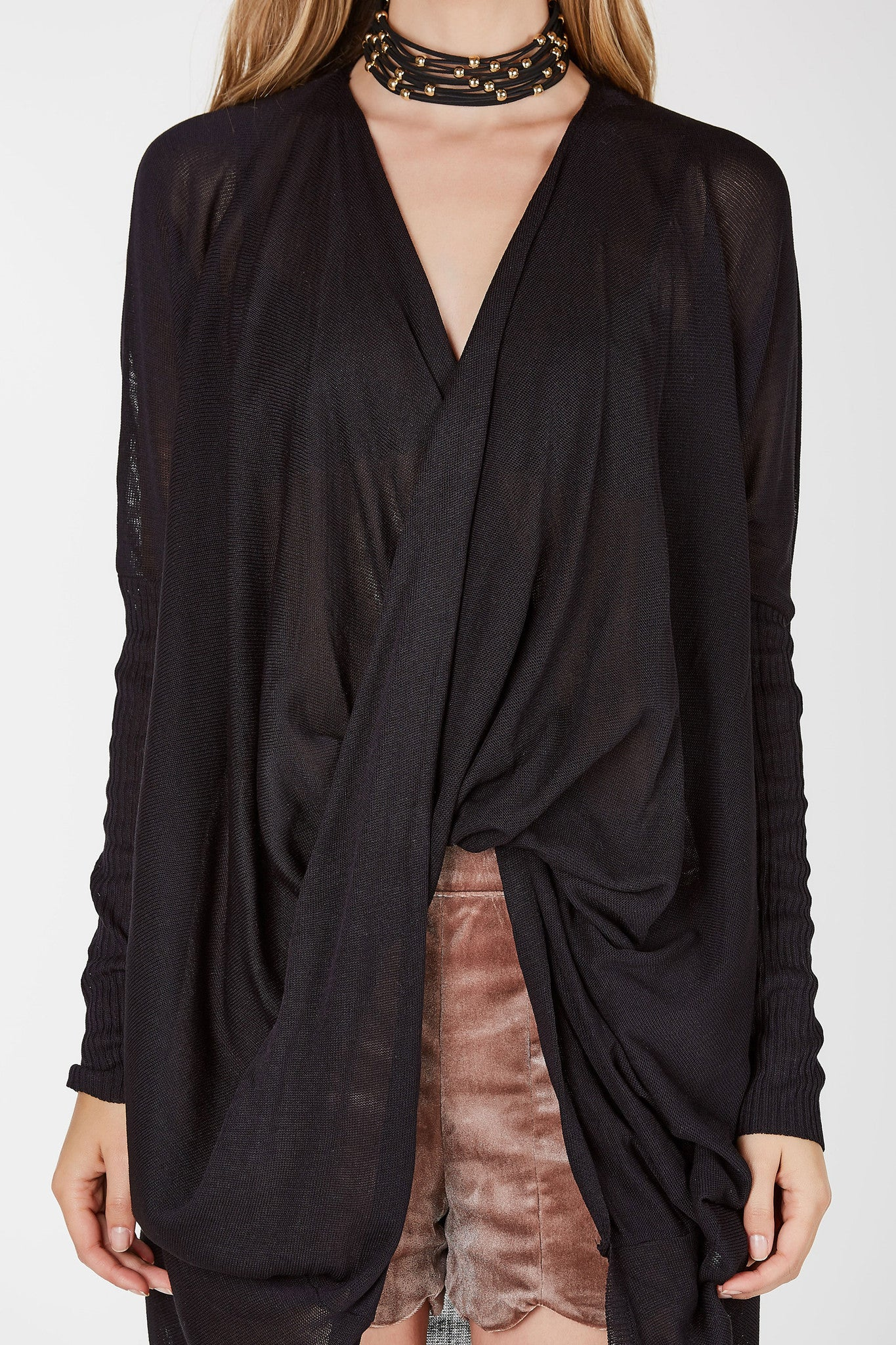 An amazing cardigan featuring a low cut neckline leading to a front twist detail. This cardigan is slightly sheer with a longer back. Long fitted sleeves even out the loose relaxed fit making this cardigan edgy yet adorable. Complete your look effortlessly but throwing this cardigan over your everyday outfits.