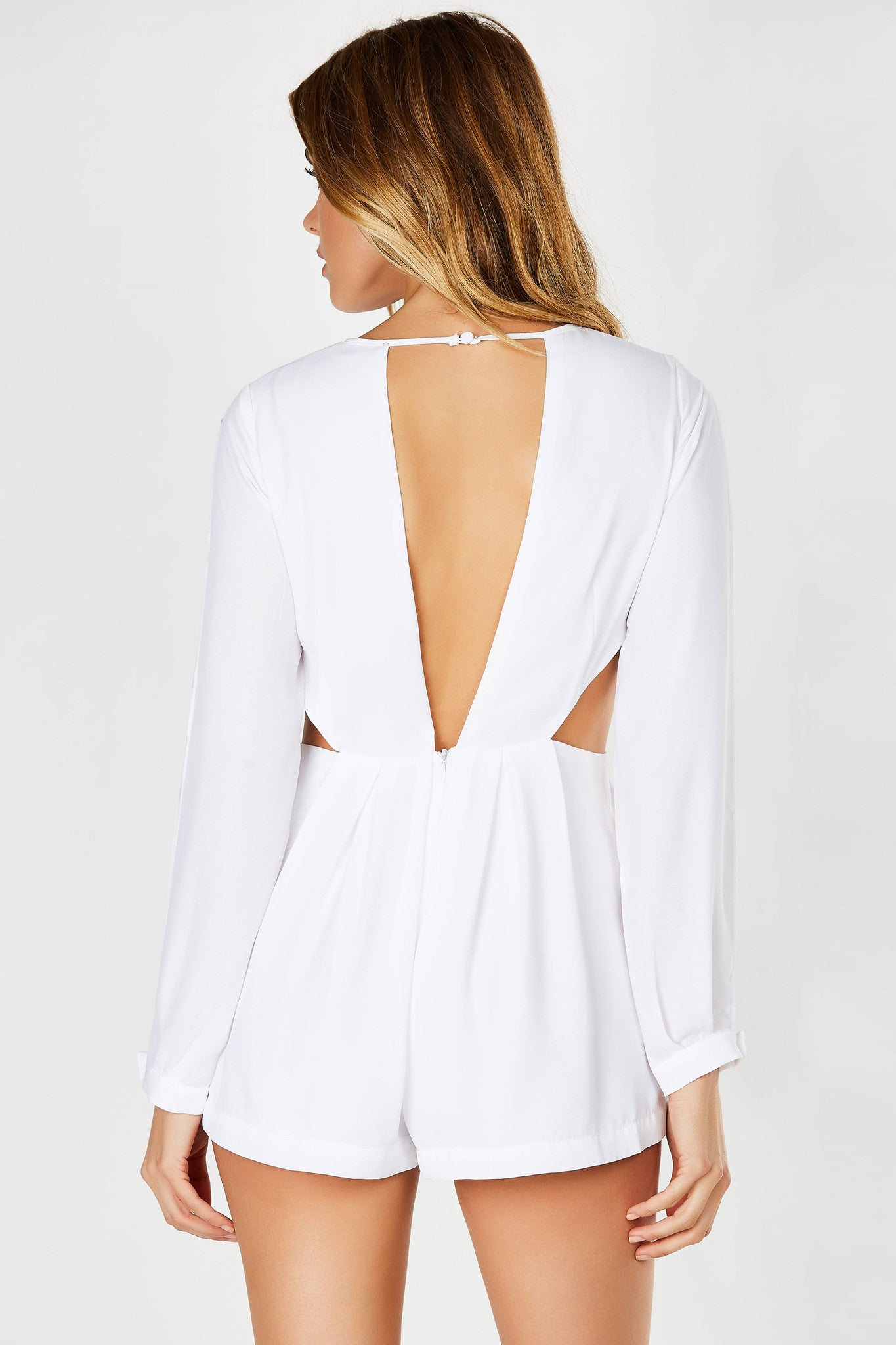 A sultry chiffon romper with daring cut outs all around. Mirrored cut in both front and back with flowy lined bottoms. Long sleeves with open slits with single button and zipper in back for closure.