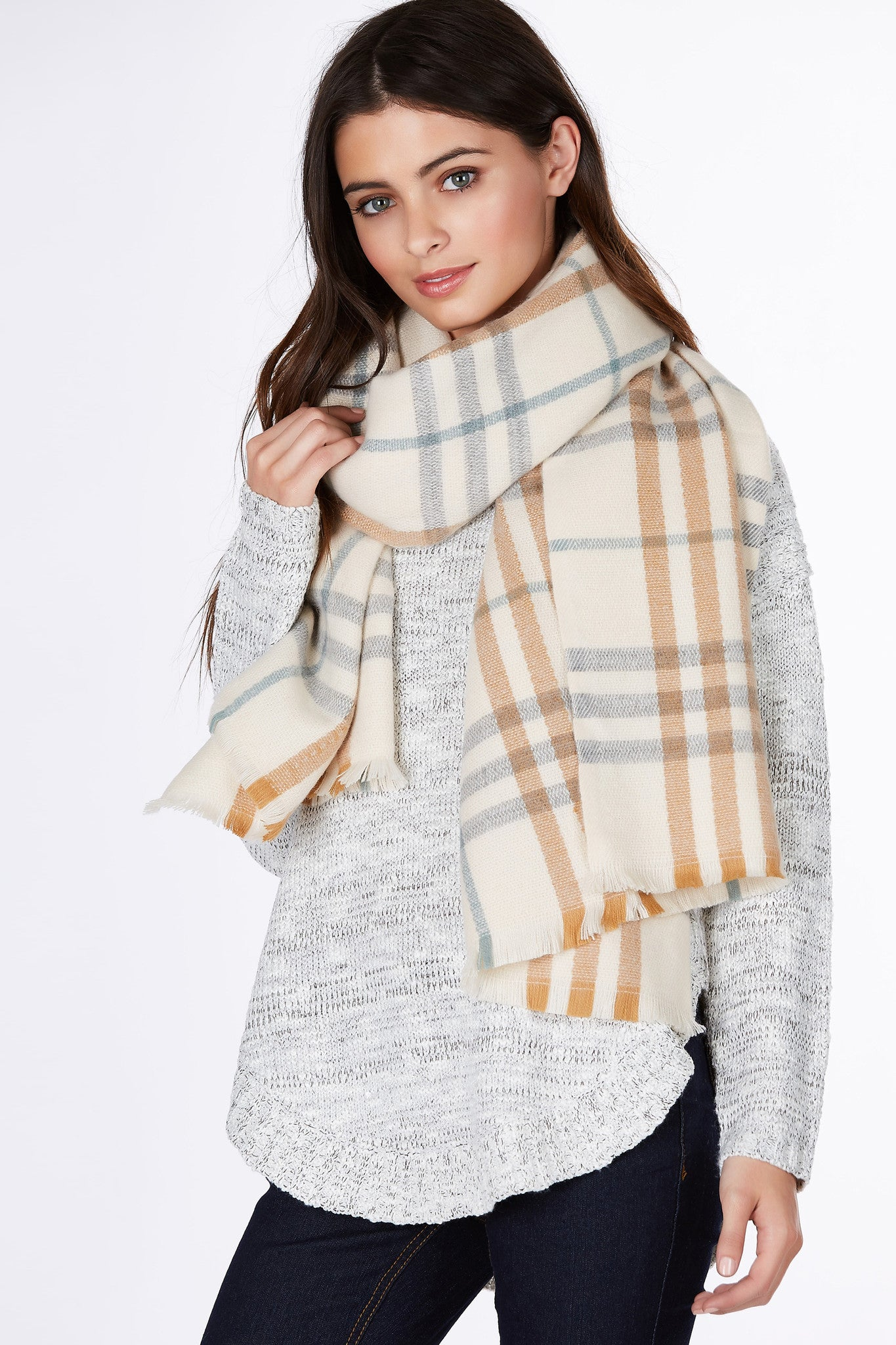 A soft oversized scarf with classic plaid pattern throughout. Delicate pastel color scheme brings a preppy vibe. Style with a basic outfit with a white tee and denim jeans.