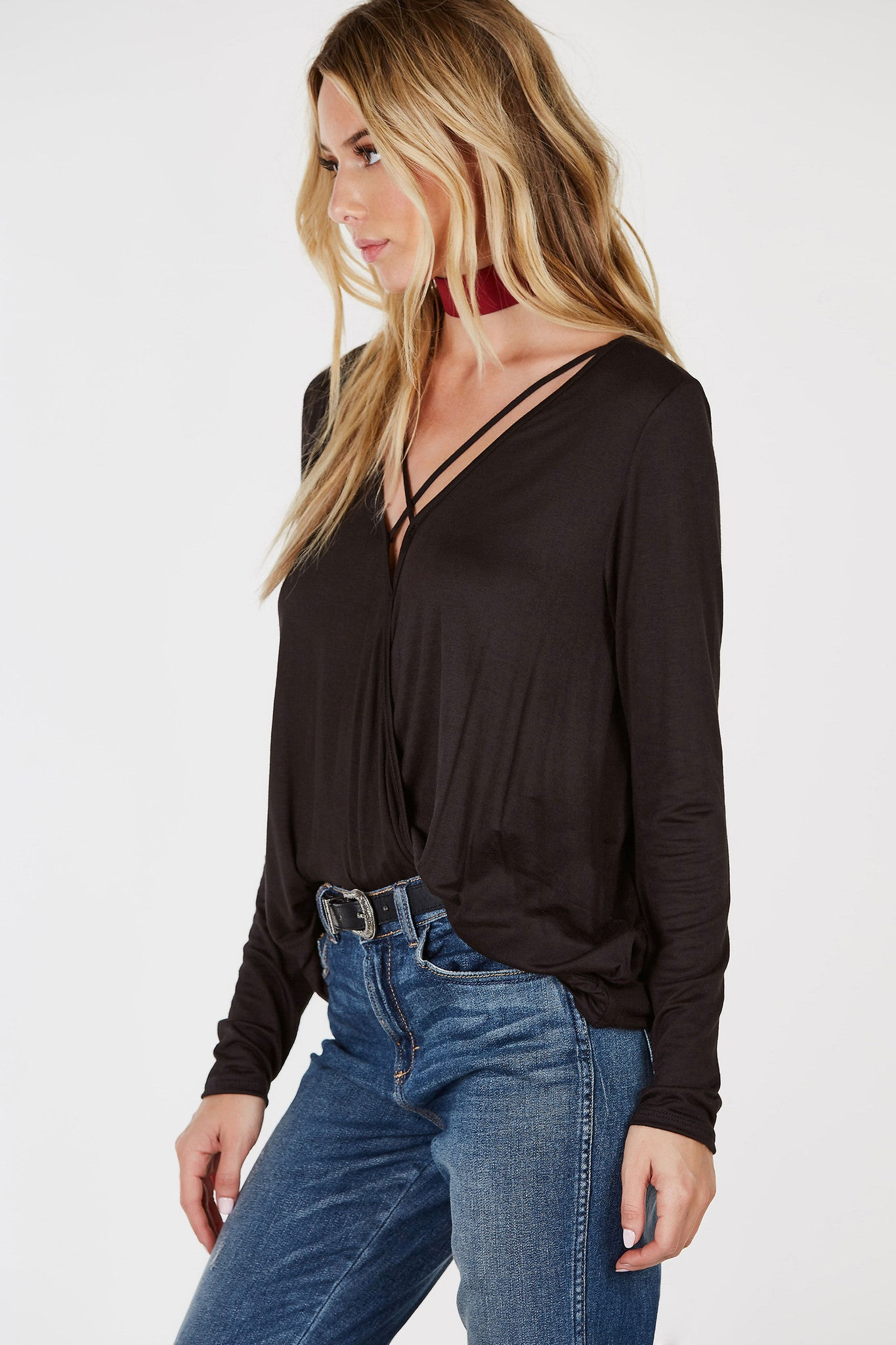 A soft lightweight top for your everyday, basic outfit. Fitted long sleeves with a relaxed body. Chic criss cross strap detailing with an overlap neckline. Draped finish in front with a longer rounded back. Style with skinny jeans and booties.