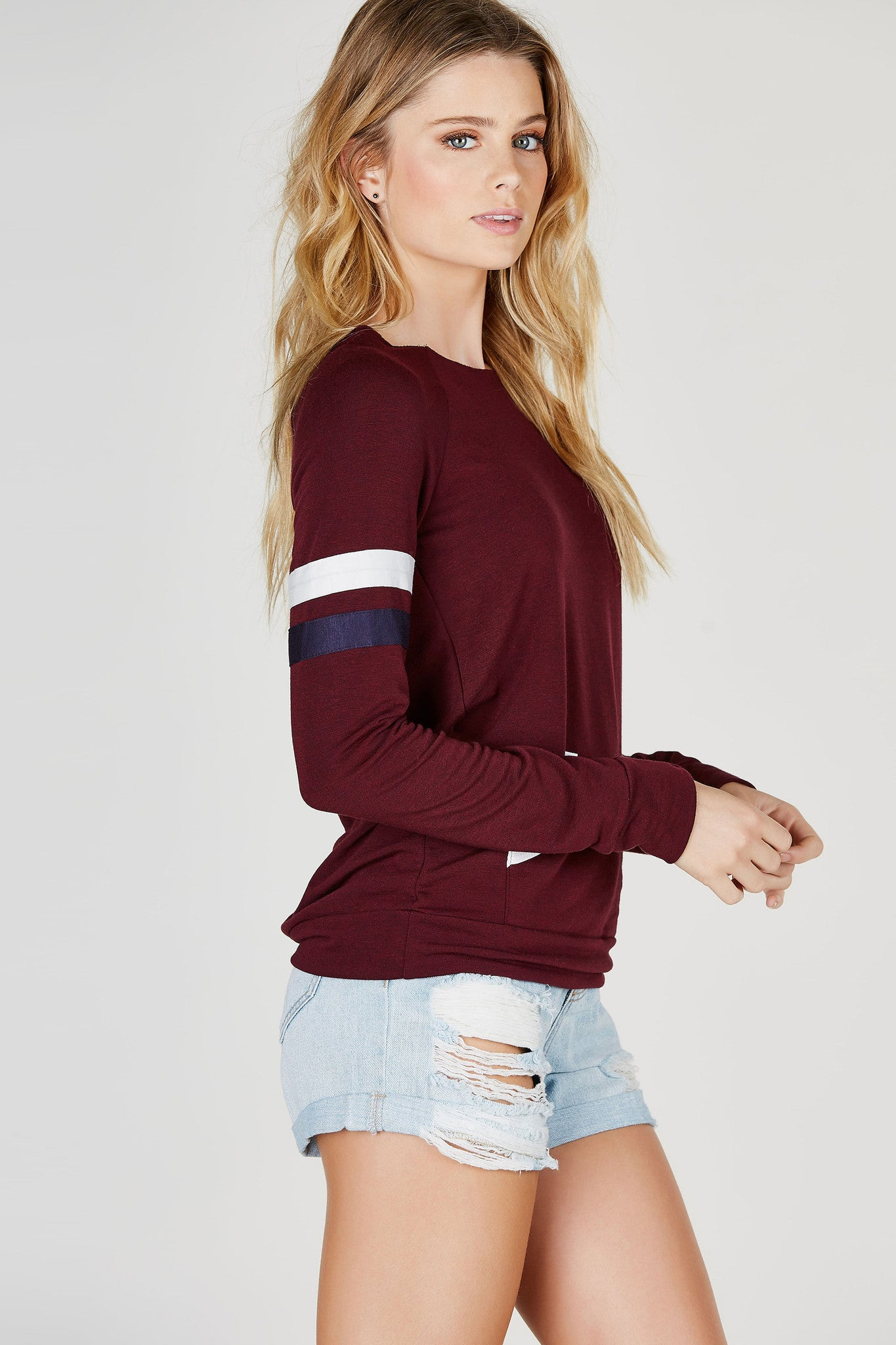 A soft long sleeve sweatshirt with contrast stripes for a casual, athletic vibe. Features a raw hem neckline with a center pocket. Slouchy fit great to style with denim cut offs and sneakers for a laid back look.