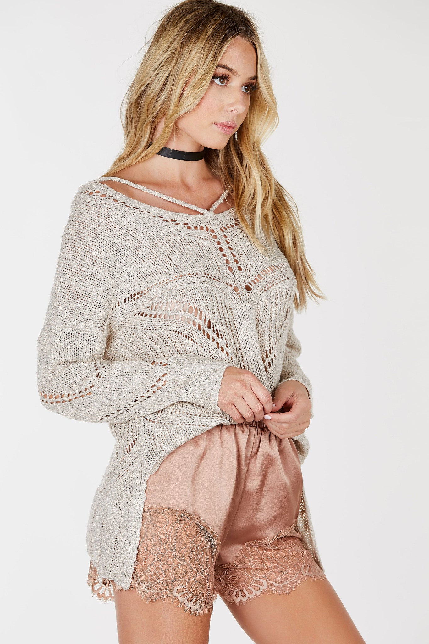 A great layering piece for Fall. This loose knit sweater features peek-a-boo patterns throughout with multi strap detailing in both front and back. Comfortable loose fit at body with slim fit long sleeves. Scooped back with slit detailing for a chic finish.