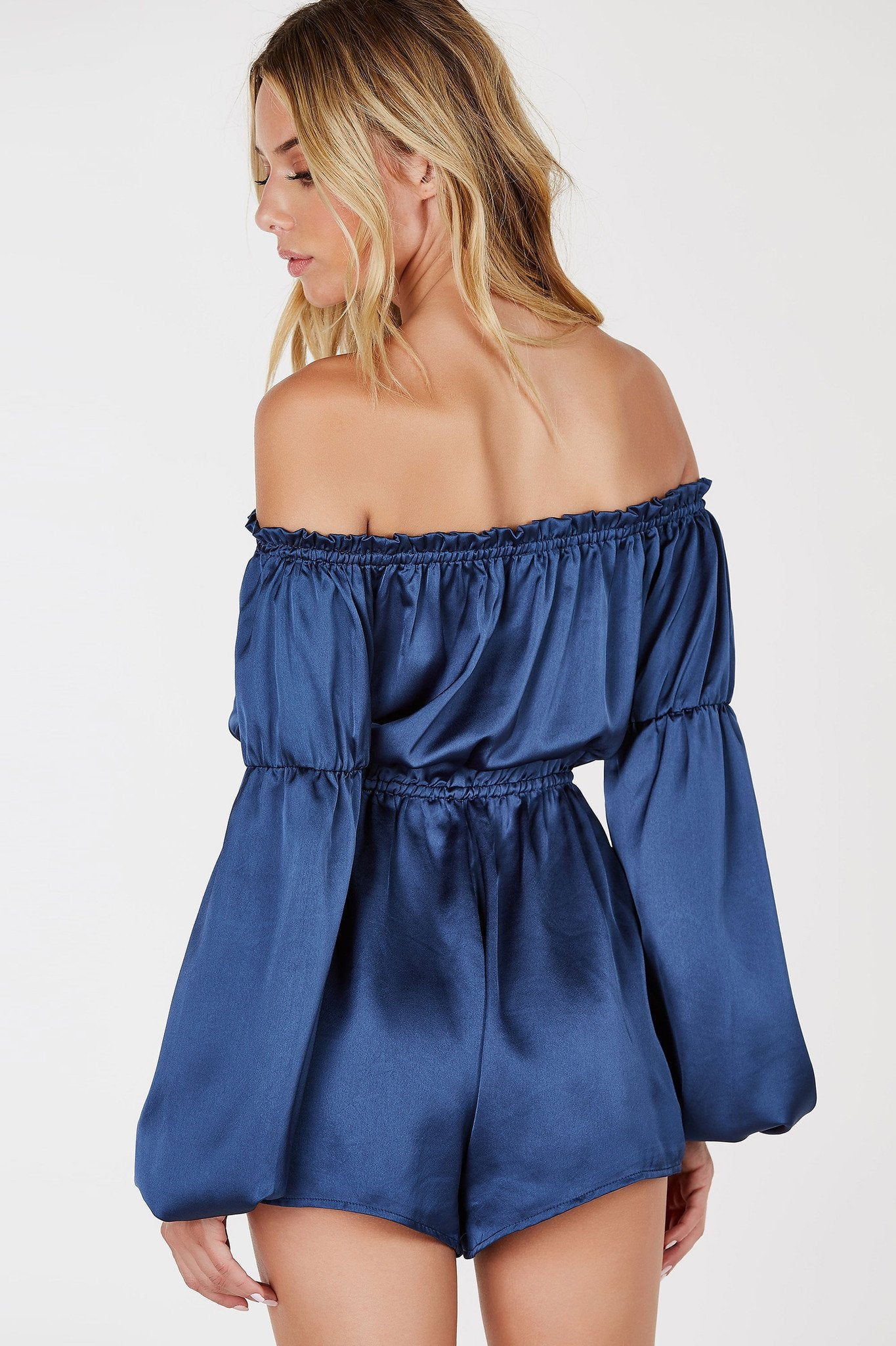 A lovely off shoulder romper with a gorgeous satin finish. Flirty ruffle detailing on top with a bold cut out in front. Features ties with chic tassels at ends for added detail. Elasticized at the waist to accentuate your curves.