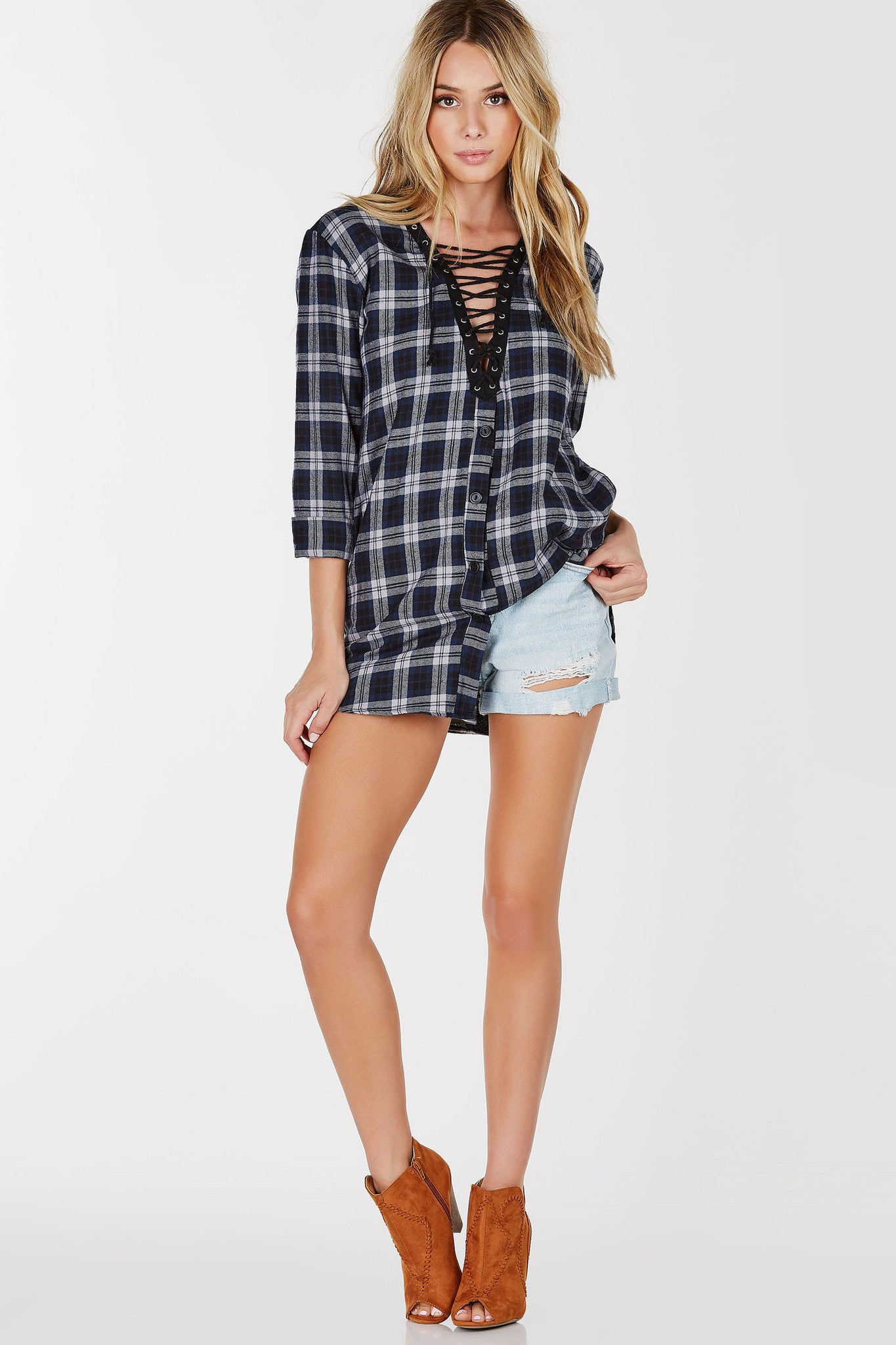 A super comfortable plaid tunic with a trendy lace up design. Features faux buttons below the neckline for a flannel vibe. Soft rounded hem brings a casual vibe. Style with sneakers and a denim jacket!