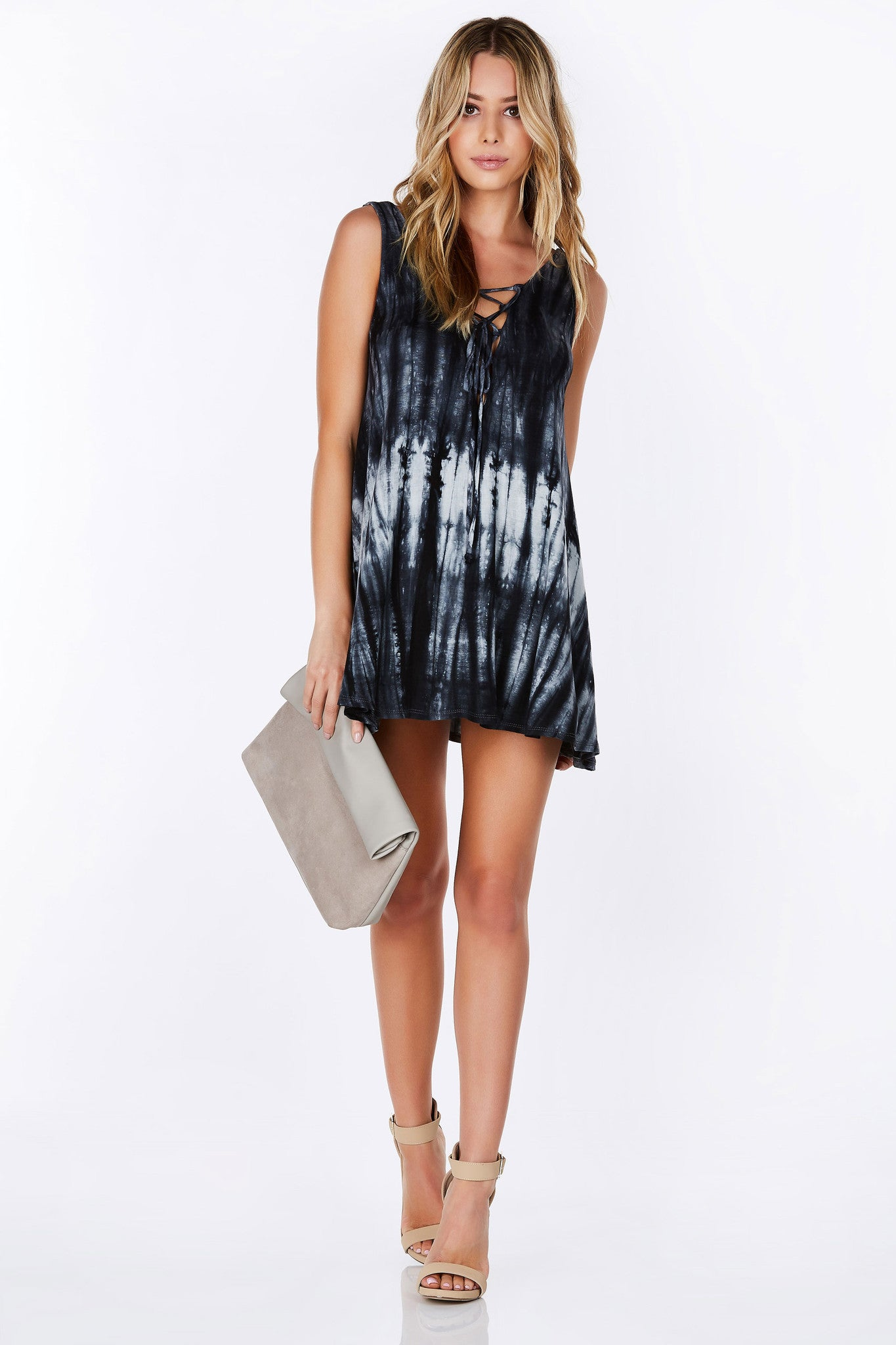 Trendy lace up front with a sexy scooped back. Providing a flattering loose fit, this tie-dye tunic is perfect to pair with skinny jeans or simply throw on over a bathingsuit. Keep cool and chic all Summer long by adding this to your wardrobe.