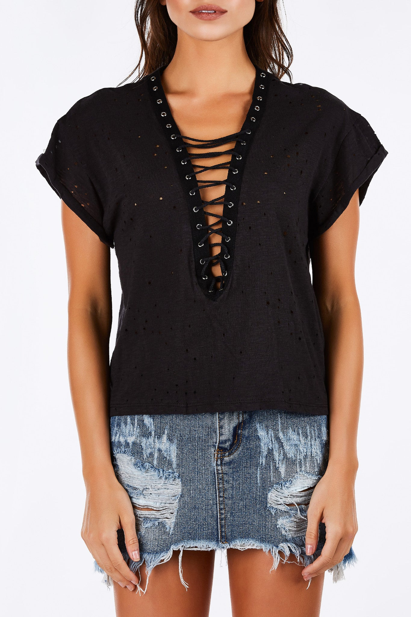 Distressed with a comfortable relaxed fit. Trendy lace up neckline for a soft grunge feel. Lightweight, breathable material to keep you cool during the heat. Pair with denim cut offs and sneakers for a street-style look.