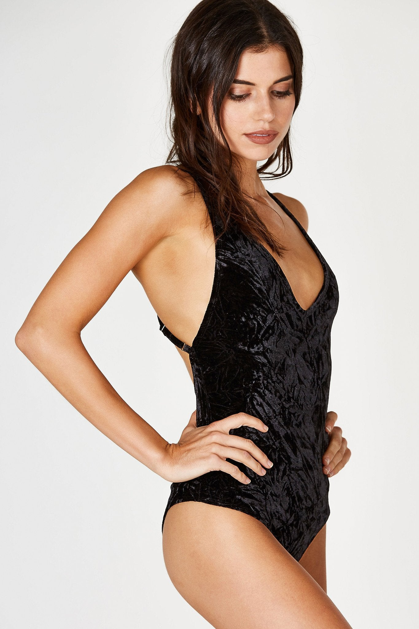 A stunning V-neck bodysuit with a gorgeous velvet finish. Slim fit with enough stretch for comfort. Open back with adjustable shoulder straps that criss crosses for a seductive vibe. Cheeky cut with snap on buttons for closure at bottom. A great going out piece for Summer nights.