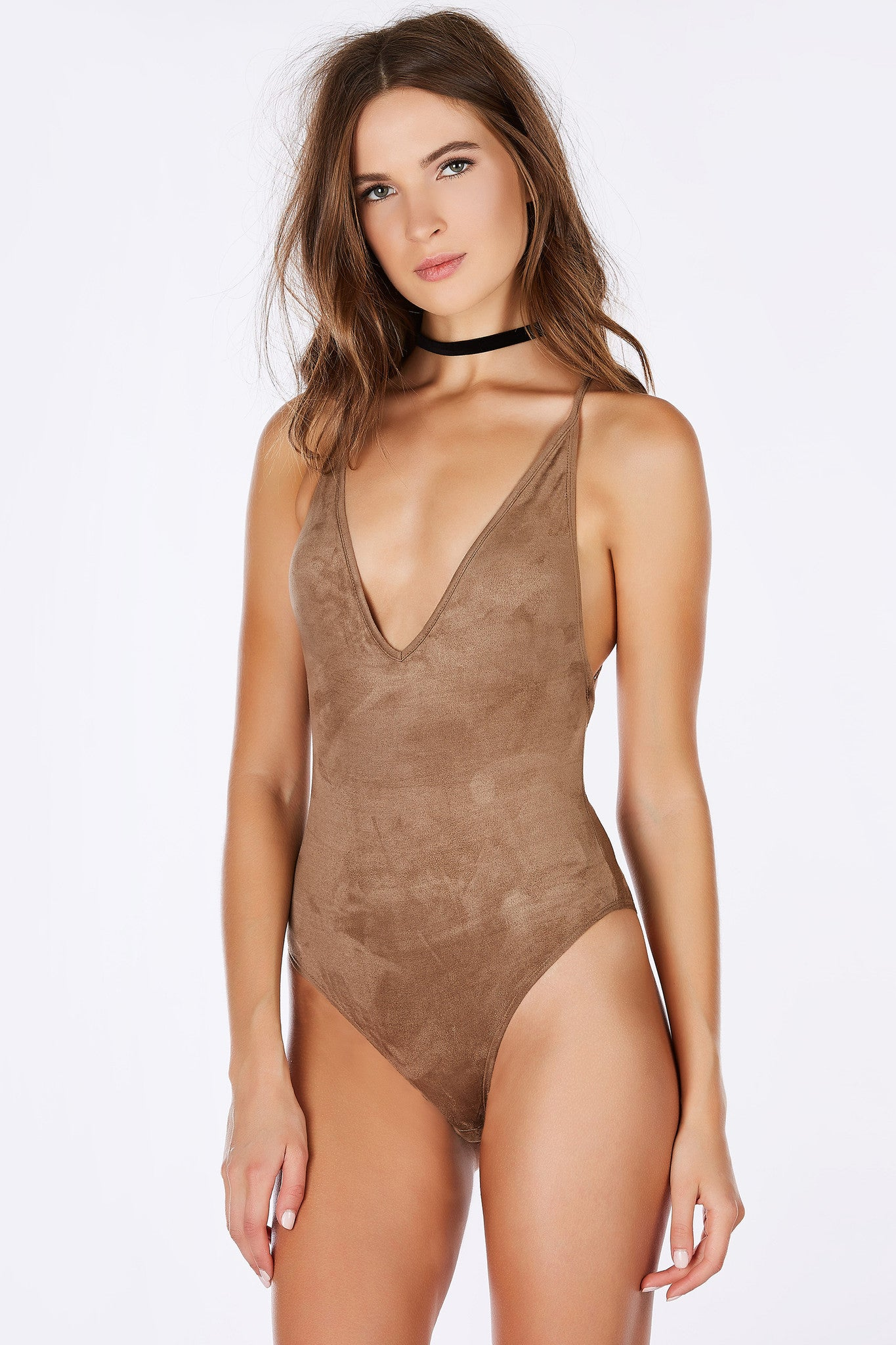 A sexy V-neck bodysuit with a chic suede finish. Stretchy material with an amazing fit. Adjustable shoulder straps that criss crosses in the open back. Pair with skinny jeans with ankle strap pumps for a seductive evening look.