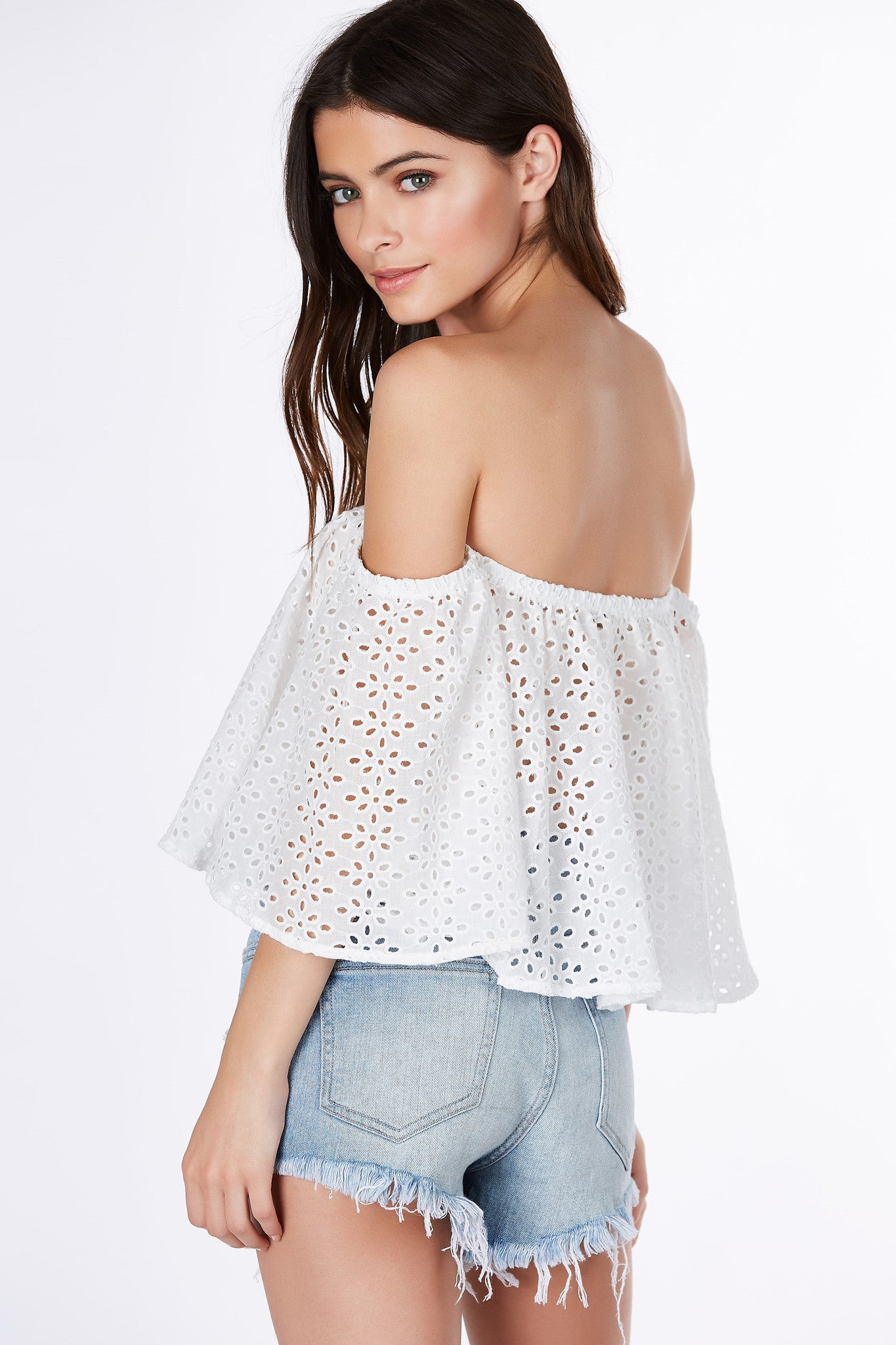 This off shoulder crop top is perfect for when you're feeling sweet and innocent. Adorable short sleeves with comfortable elasticized neckline. Dainty daisy patterns throughout with a chic peek-a-boo effect. Pair with mom jeans and sandals for a vintage-esque look.